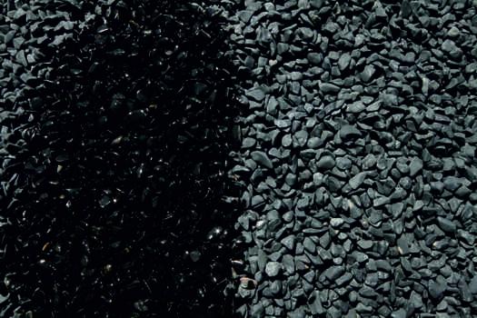 Canto rodado negro natural, mojado y seco.